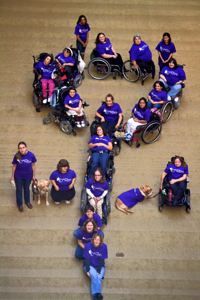 Photo from an overhead perspective of a bunch of young women with disabilities,many in wheelchairs, all wearing purple t-shirts, they formed a female symbol