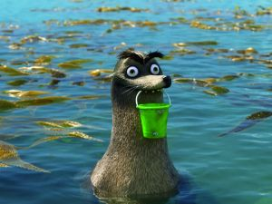 """An animated scene from the Pixar film """"Finding Dory."""" Gerald the sea lion in a kelp bed holding a green plastic pail in his mouth."""