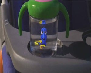 "An animated scene from the Pixar film ""Finding Dory."" A cupholder of a baby stroller with a sippy cup that has a blue tang inside."