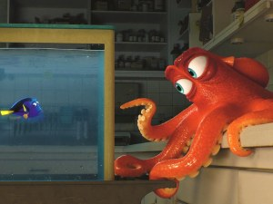 """An animated scene from the Pixar film """"Finding Dory."""" In an aquarium, a blue tang fish is in a fishtanks looking at an octopus staring on top of a kitchen counter"""