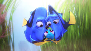 "An animated scene from the Pixar film ""Finding Dory."" Two parents who are blue tang fish embracing their little baby fish in the center."
