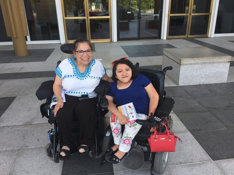 Image of Sandy Ho, a young Asian American woman in a wheelchair. On her left is Judy Heumann, an older white woman in a wheelchair.