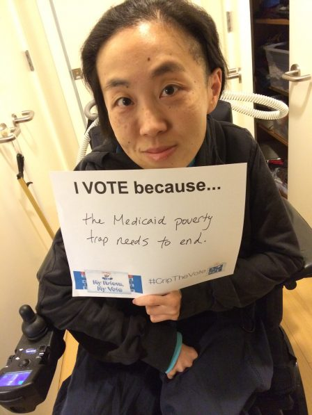 "Photo of an Asian American woman in a wheelchair holding a white piece of paper that says, ""I Vote because...the Medicaid poverty trap needs to end."""