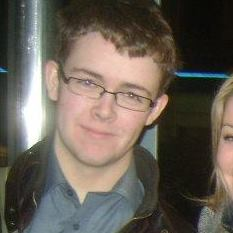 Young white man with short sandy brown hair. He is wearing glasses and a blue button-down shirt. Over his shirt, he has a brown leather jacket. To the right of the image, a face of a white woman with blonde hair is partially cut off from the photo.