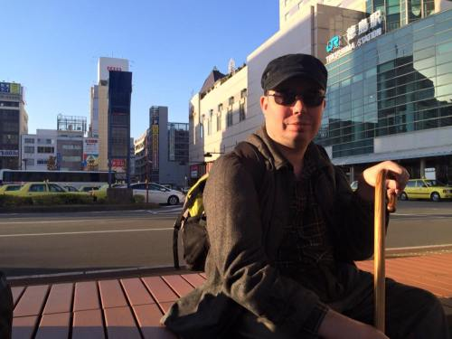 A white man sitting on a bench with a cane. He is wearing dark sunglasses and has a black cap on his head. Behind him is an urban landscape of a city in Japan