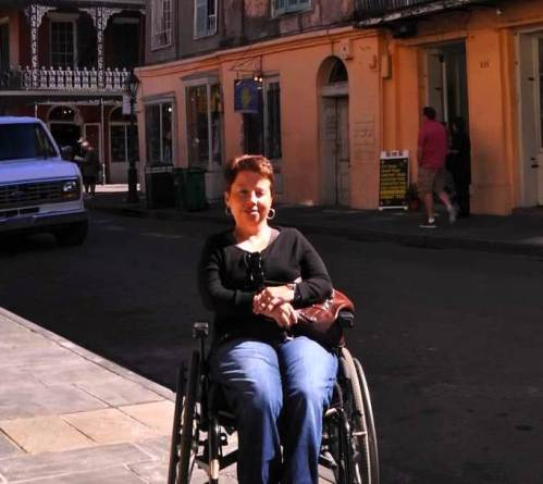 Outdoor photo of a white woman in the French Quarter of New Orleans, Louisiana. She has short, cropped brown hair, gold earrings and is wearing a long-sleeved black shirt and blue denim jeans. She is sitting in a manual chair and there are historic buildings behind her.