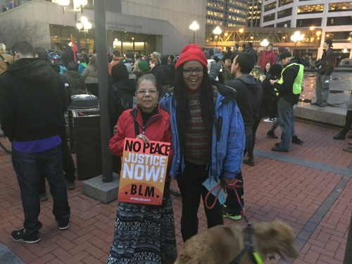 "Two women of color at an outdoor protest. One is holding a sign that says, ""No Peace. Justice Now! BLM"" The other woman is holding the leash with a dog"