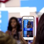 Photo of a person holding a smartphone taking a photo of First Lady Michelle Obama at a rally.