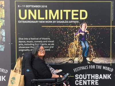 """Profile view of an Asian woman in black wheelchair. She has a brown shopping bag hanging on the back of her wheelchair. Behind her is a large billboard for """"Assisted Suicide: The Musical"""" showing at the Southbank Centre in London. The word UNLIMITED is in gold. The billboard shows a thin petite white woman in a gold manual wheelchair sprinkled in gold confetti."""