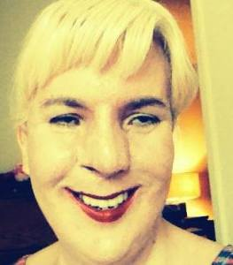 Image of Jennifer Justice, a white woman with short blonde hair. She is wearing bright red lipstick and is smiling at the camera. Her image has a filter that gives a yellow tint.