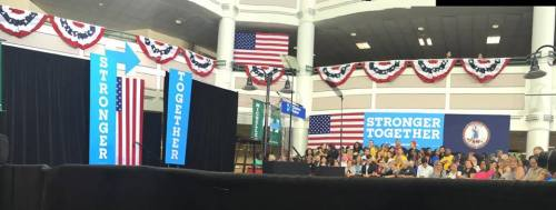"""Photo of the stage at George Mason University that has a lectern and signs that say, """"Stronger Together"""". Patriotic bunting and American flags are in the background."""