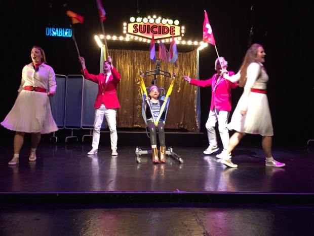 """Photo of stage performance of """"Assisted Suicide, the Musical"""" The main character, a thin, petite white woman is Liz is seated in a hoyer lift on centre stage. There is gold curtain behind her with a sign 'suicide' in lights. Two women wearing white tops and skirts with red belts are dancing, with two men in red jackets with white trousers are holding up flags."""