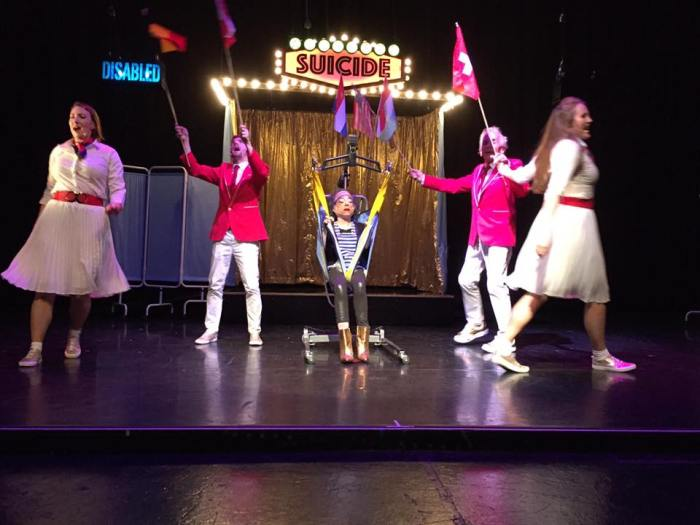 "Photo of stage performance of ""Assisted Suicide, the Musical"" The main character, a thin, petite white woman is Liz is seated in a hoyer lift on centre stage. There is gold curtain behind her with a sign 'suicide' in lights. Two women wearing white tops and skirts with red belts are dancing, with two men in red jackets with white trousers are holding up flags."