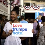 """Photo of a young woman of color with a white t-shirt on holding a sign that says, """"Love trumps hate"""" at a political rally. Behind her are crowds and a stage."""
