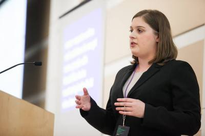 Profile of a young white woman with shoulder-length brown hair and a black blazer. She is speaking in front of a lectern. Behind her is a screen projected with a slide.