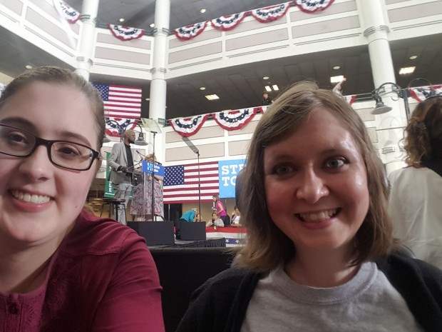 Selfie of two young white women in a large call. Behind them you can see a stage with a lectern, multiple American flags hung up and patriotic bunting on multiple floors.