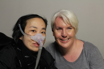 Photo of two people against a blank white background. A white woman on the right has white-blonde hair pulled back. She is wearing a scoop neck gray top. On the left side is an Asian American woman in a wheelchair wearing a black jacket and black patterned scarf. She is also wearing a mask around her nose with a tube. Both are smiling at the camera.