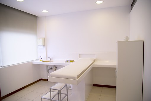 Image of an exam room that has everything in all white--white cabinets, countertops and an exam table with a small step stool.