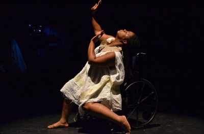Image of a self-described, 'an African American, queer, disabled, femme' sitting in a manual wheelchair. Her head is tilted back, arms and hands raised upward, her legs are resting on the ground at different angle, one leg straight while the other is bent 45 degrees. The background is completely dark.