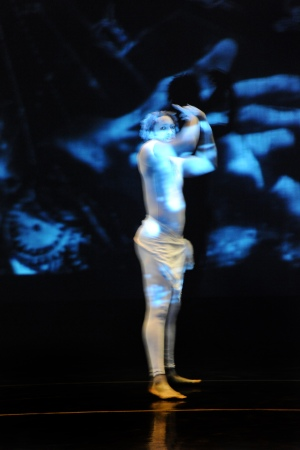 Image of a person dressed in white on stage. The person's arms are raised. A projected image is projected over the person's body in different shades blue.