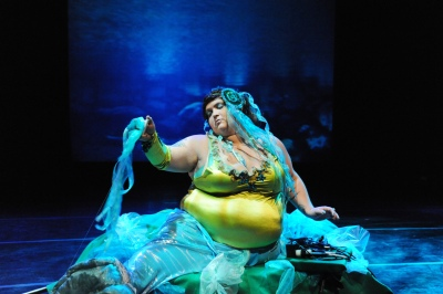 Large woman sitting on a stage dressed in bright colors aqua colored fabric flows over her legs, she has aqua hair extensions as well. She looks like a dreamy sea creature. Her top is a form-fitting tank style in bright citron yellow-green. Behind her are blue lights on the stage.