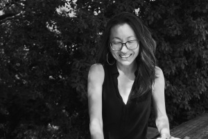 Black and white photo featuring a young queer disabled Korean woman. She is wearing glasses and a black v-neck tank top. She is standing in front of a bunch of trees with leaves all around her.