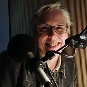 A white woman with short white hair inside a recording booth. There is a microphone in front of her and light from the corner illuminating the right-half of her face. She is wearing a dark-colored long-sleeve shirt and eyeglasses. She is smiling at the camera.
