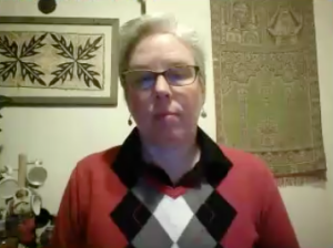 A white woman with short white hair. She is wearing glasses, an argyle sweater that's red, gray, black and white, and a pair of earrings. She is speaking to a web cam. Behind her are two tapestries hanging on the wall and a several coffee mugs.