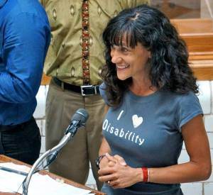 Image description: A white woman with long, curly hair smiles broadly, with raised eyebrows, and speaks into a microphone on a podium. She clasps her hands together tightly and looks out at her audience. Her t-shirt is decorated with