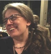 Image of an older white woman with glasses, her long hair is puled back and resting on one shoulder. She is looking away from the camera and smiling. She is wearing a dark-colored shirt and a necklace.
