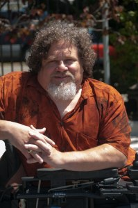Photo of a man in a wheelchair, turned so his arms are resting on one side of the wheelchair's armrest. He is an older white man with brown curly hair and a white beard. It is a sunny day and he is wearing a short sleeved orange shirt with a pattern.
