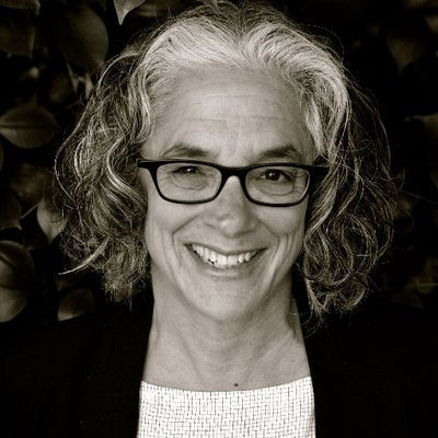 A black-and white photo of an older white woman with dark-colored eyeglass frames, shoulder-length curly hair that's white and gray. She is standing behind a dark background wearing a black blazer and a white scoop neck top. She is smiling at the camera. Photo credit: Ahri Golden