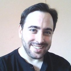 A young white man with dark brown short hair. He has a half-grown beard and is wearing a black shirt. He is smiling at the camera.