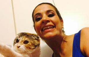 Young Palestinian American woman with her hair pulled back. She is wearing a blue tank top and smiling at the camera. On the left side of the images a Scottish fold cat that is white with streaks of brown and black.