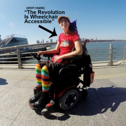 Outdoor photo by the water, a young white woman dressed in rainbow-striped leggings, a red t-shirt and hat is in her wheelchair. She also has a hat and eyeglasses on. In the image is text with a black arrow pointing at her that reads: (shirt reads)