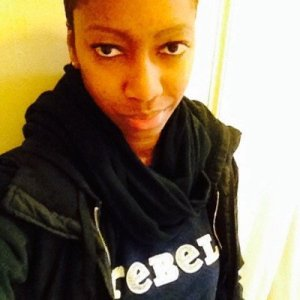 """TL , a black person with short hair takes a selfie while wearing a black hoodie & black scarf with a navy shirt that has white words """"REBEL."""""""
