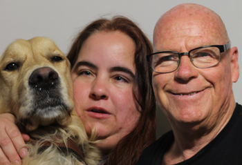 A photo featuring Maia Scott, Ron Jones, and Maia's guide dog was taken on August 14, 2014: close up portrait of a guide dog, a woman and man all sitting next to each other looking at the camera. The guide dog on the far left is a golden retriever with its nose and face pointed at the camera. The woman in the middle appears to be white and has long brown hair. The man on the right appears to be white, is bald, wearing glasses, dressed in a black shirt, and smiling at the camera.