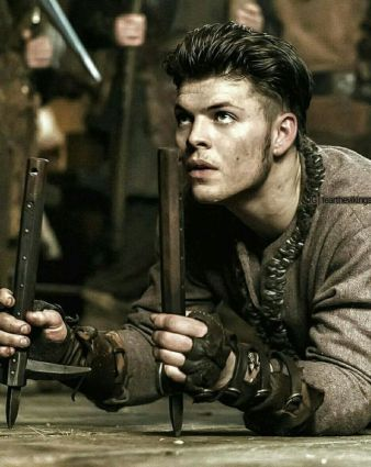 Image description: screenshot from an episode of Vikings, an original series on the History Channel. Ivar the Boneless is a young Viking warrior with short dark hair. He is on the floor in a crawling position. He is looking upward. In both of his hands he is holding sharp wooden sticks to help pull his body forward when crawling.