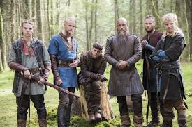Image description: screenshot from an episode of Vikings, an original series on the History Channel. Ivar the Boneless is a young Viking warrior with short dark hair. He is in the center, sitting on a tree stump. To the left of him are his brothers Hvitserk and Bjorn. To his right is his father Ragnar and brothers Ubbe and Sigurd.