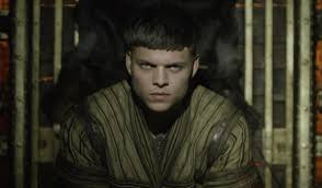 Image description: screenshot from an episode of Vikings, an original series on the History Channel. Ivar the Boneless is a young Viking warrior with short dark hair. He is staring intensely at the camera with menace.