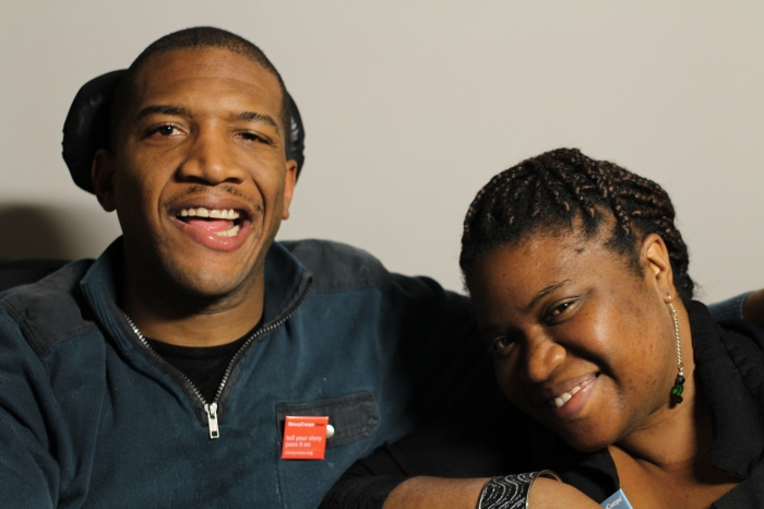 Image Description: A photo featuring Lateef McLeod and Aqueila Lewis, taken on March 5th, 2015. Lateef McLeod is on the left, wearing a zip-up blue fleece, a black tee-shirt, and a red StoryCorps pin. Lateef appears to be African American, and he is smiling. Aqueila Lewis is on the right, wearing a black sweater, a long earring, and her hair is braided and pulled back. She appears to be African American, her face is tilted to the left, and she is smiling.