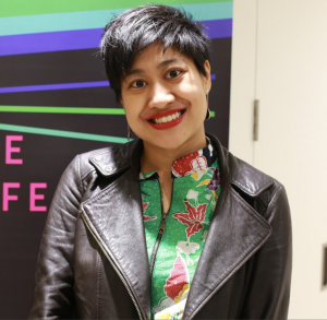 Image description: Khairani Barokka, a young Indonesian woman with short black hair. She is wearing a black leather jacket with a multicolored shirt inside. Behind her is a poster that is black with horizontal lines in green, blue, and purple.