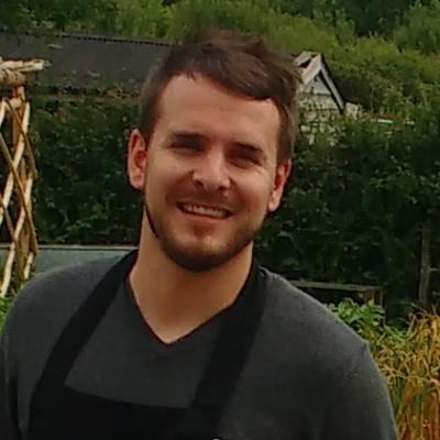 Photo of a white man with short brown hair and beard. He is wearing a dark gray v-neck t-shirt and black apron. Behind him are trees and a house.