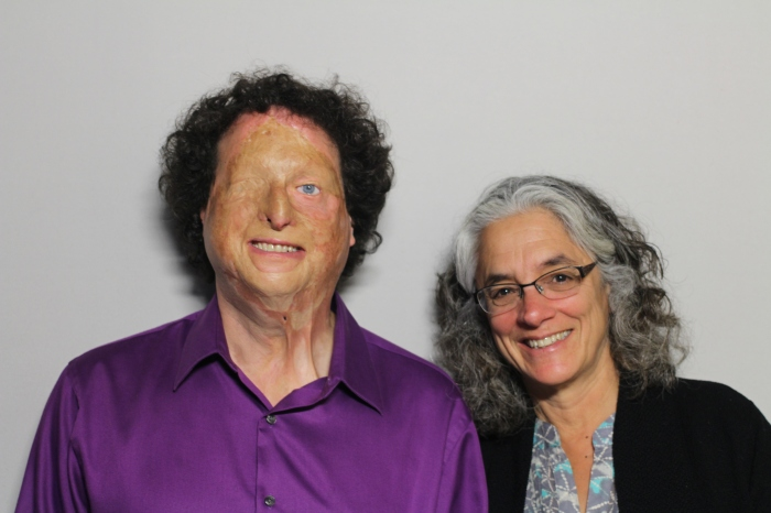 Image Description: A photo featuring Joshua Miele and Lainey Feingold taken on August 21, 2014. The man on the left is Joshua Miele. He appears to be white, and is wearing a purple button-up shirt. He has curly brown hair, one blue eye and scars on his face. He is looking at the camera and smiling. The woman on the right is Lainey Feingold. She appears to be white, has medium-length salt and pepper hair, and is wearing glasses with a black cardigan and a blue shirt. She is looking at the camera and smiling.