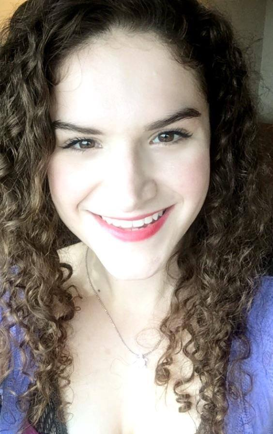 A photo of Lillie Lainoff taken in July 2016. She appears to be white and is wearing a purple shirt and a sea turtle necklace. She has long, curly brown hair and is smiling at the camera.